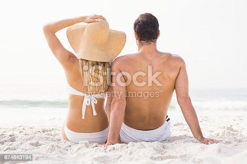 istock Happy couple sitting on the beach 674643194