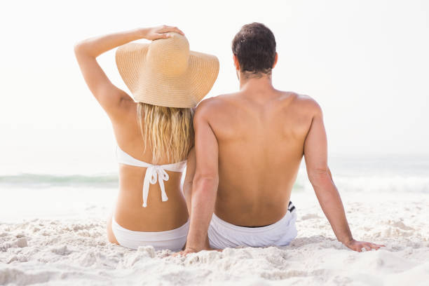 Happy couple sitting on the beach Happy couple sitting on the beach on a sunny day swimwear stock pictures, royalty-free photos & images