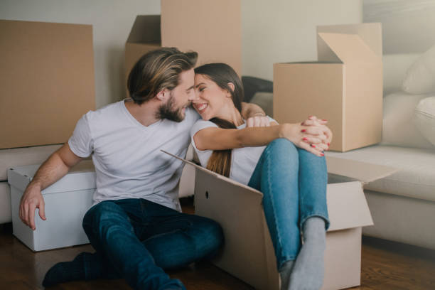 Happy couple sitting on the floor in their new living room stock photo
