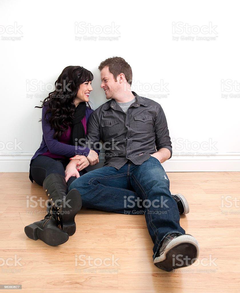 Coppia felice seduto sul pavimento parlare foto stock royalty-free