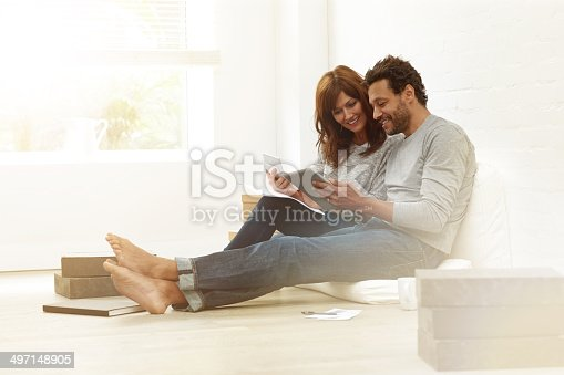 istock Happy couple sitting together calculating their expenses 497148905