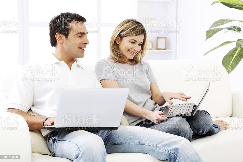 Happy couple sitting together on a sofa , using laptops. royalty-free stock photo