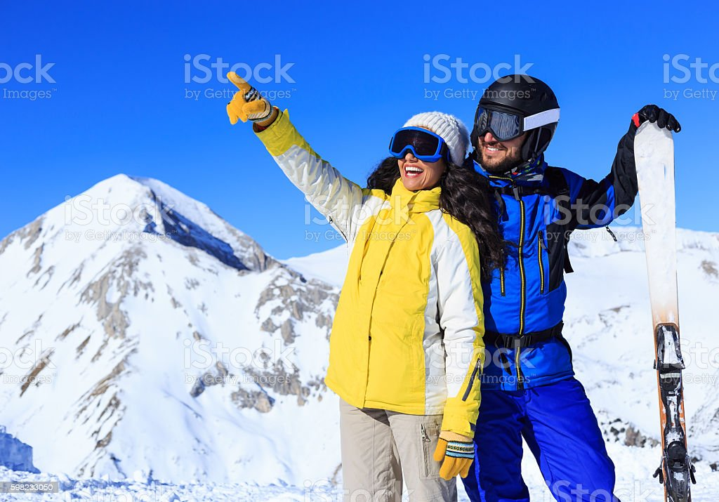 Happy couple skiers resting on top of the snow mountain foto royalty-free