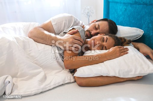 Young couple sleeping in bed under blanket. Young adult couple sleeping peacefully on the bed in bedroom. Young man embracing woman while lying asleep in bed.