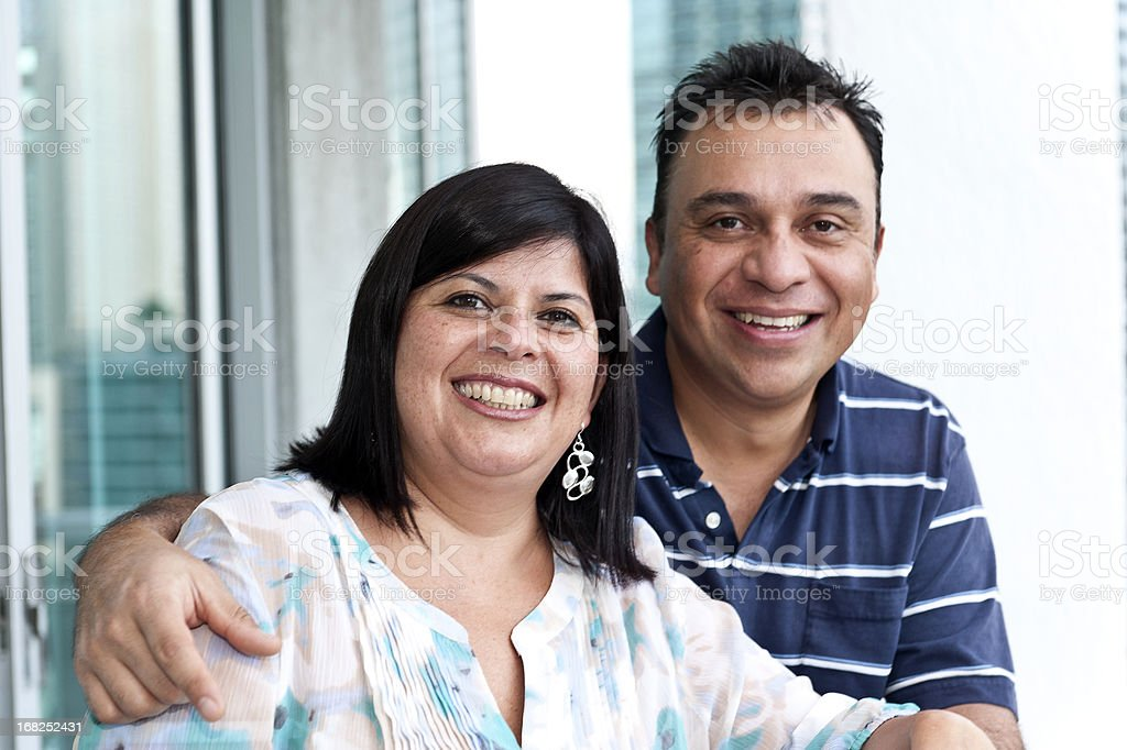 Happy couple smiles in front of a bright window stock photo