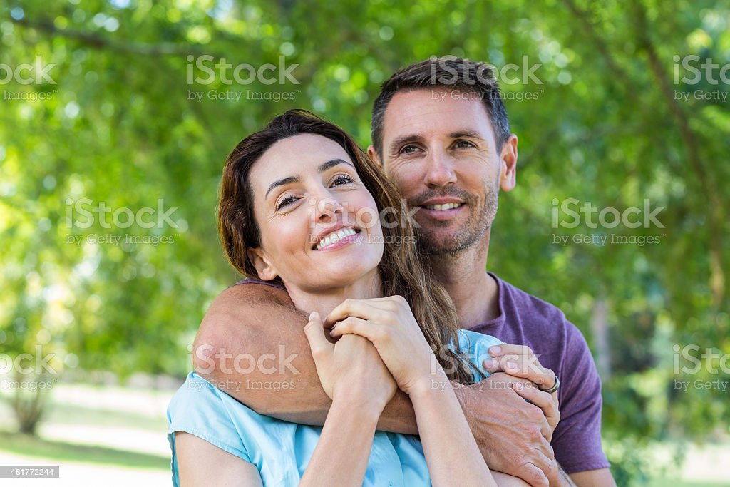Szczęśliwa para uśmiecha się do kamery w parku – zdjęcie