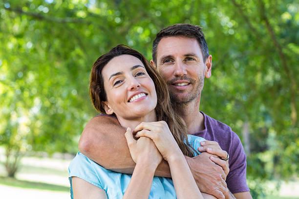 happy couple smiling at camera in park - 30 39 jaar stockfoto's en -beelden