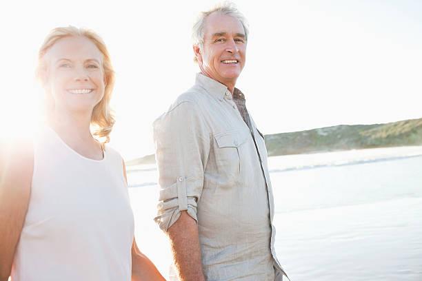 happy couple smiling on beach - vrouw 60 stockfoto's en -beelden