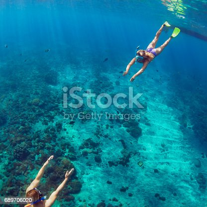 istock Happy couple snorkeling underwater over coral reef 689706020