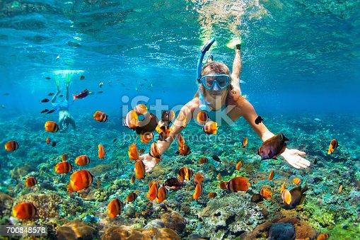 istock Happy couple snorkeling underwater over coral reef 700848578