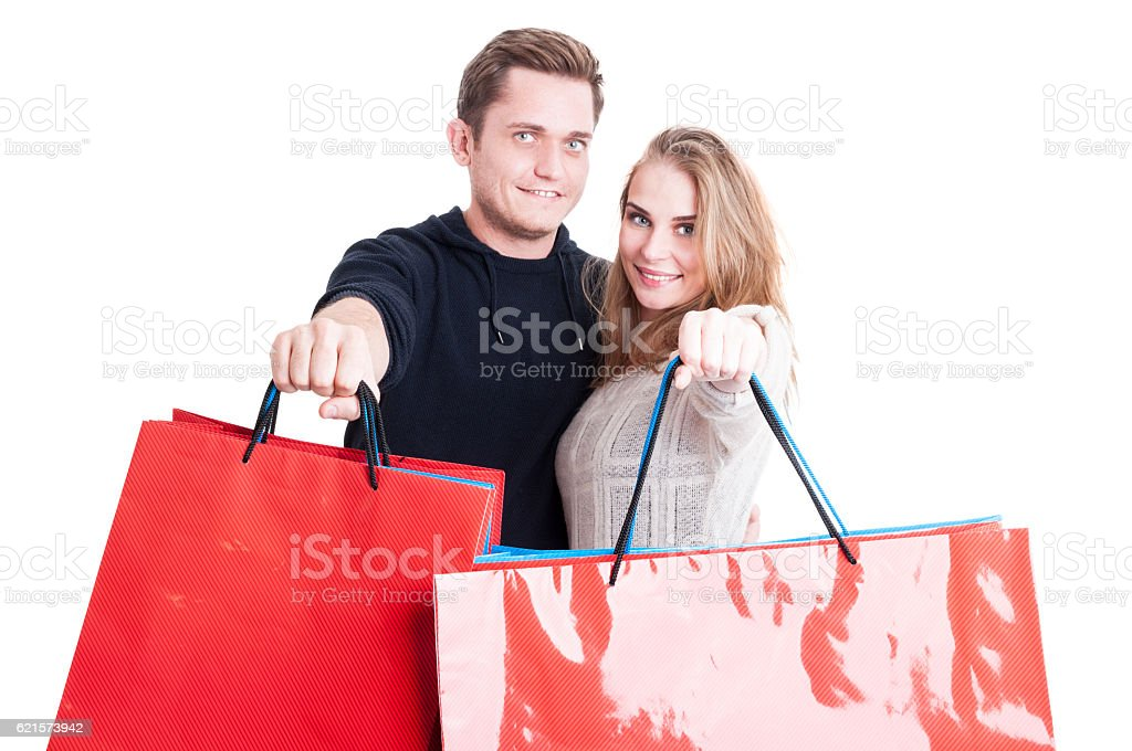 Happy couple standing and showing bunch of shopping bags photo libre de droits