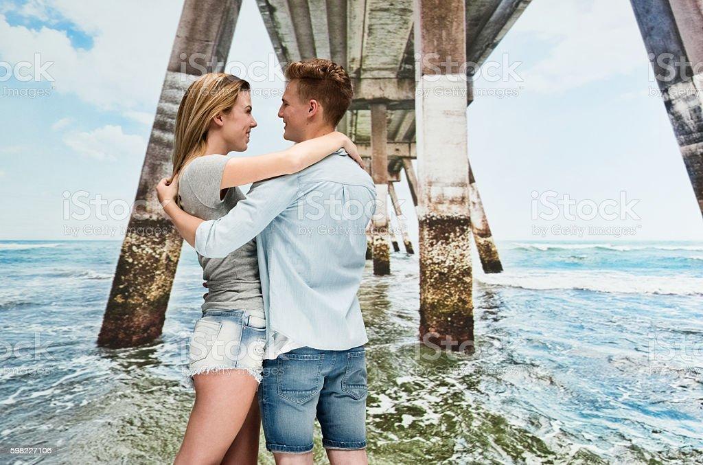 Casal feliz em pé na praia foto royalty-free