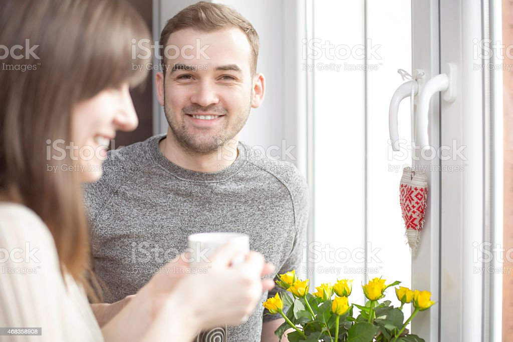 Happy couple standing at the window with coffee royalty-free stock photo