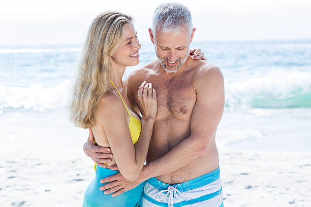 Happy couple standing by the sea and hugging each other Happy couple standing by the sea and hugging each other at the beach middle aged women in bikinis stock pictures, royalty-free photos & images