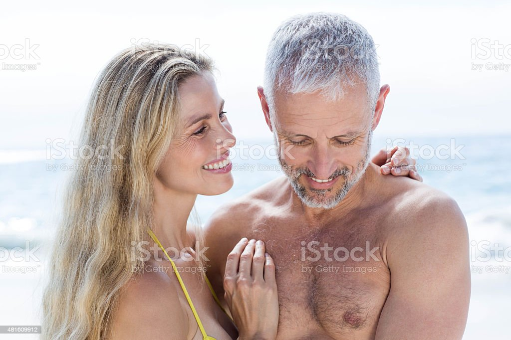 Happy couple standing by the sea and hugging each other stock photo