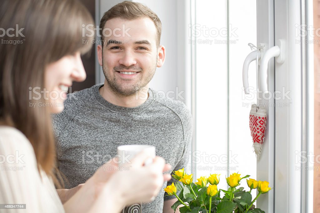 Happy couple standing by the window with coffee royalty-free stock photo