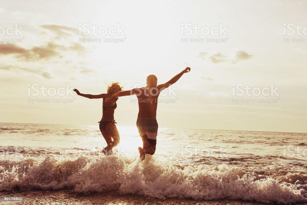 Puesta de sol playa feliz pareja ejecutar - foto de stock