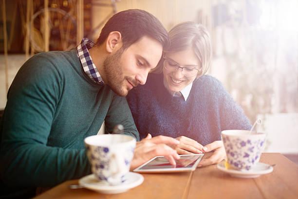 happy couple surfing on tablet - suche freundin stock-fotos und bilder