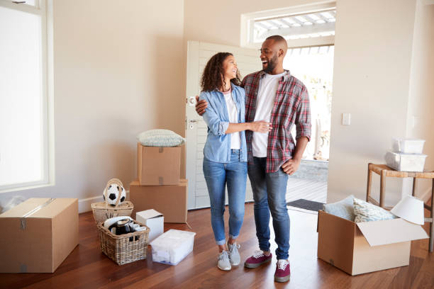 happy couple surrounded by boxes in new home on moving day - home ownership stock pictures, royalty-free photos & images