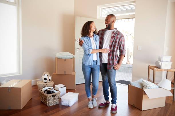 快樂的情侶被盒子包圍在新家的搬家日 - 物業產權 個照片及圖片檔