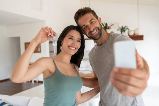 그들의 새로운 집의 열쇠를 들고 selfie을 복용 하는 행복 한 커플 - home 뉴스 사진 이미지