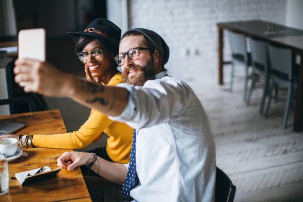 happy couple taking a selfie in cafe - ehepaar tattoos stock-fotos und bilder