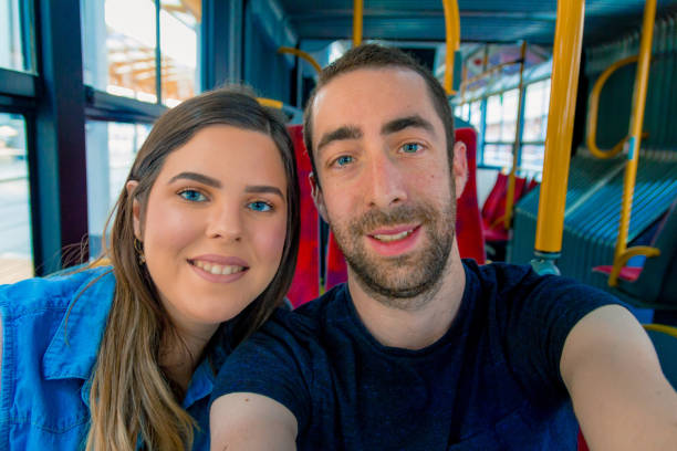 Happy couple taking a selfie with smartphone or camera inside a city bus stock photo
