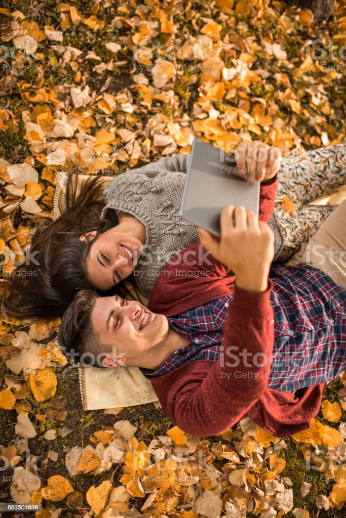 Happy couple taking a selfie with touchpad while relaxing in autumn leaves. stock photo