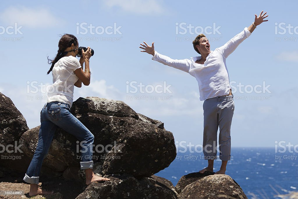 Happy Couple Taking Photo on a Cliff in Hawaii stock photo