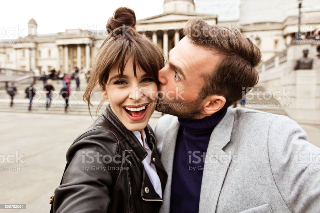 Happy couple taking selfie in front of National Gallery in London stock photo