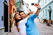 Happy couple taking selfie on the street during vacation in Europe