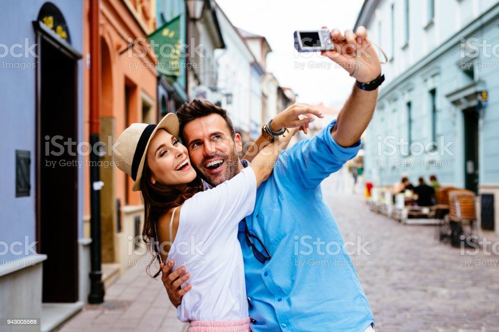 Happy couple taking selfie on the street during vacation in Europe stock photo