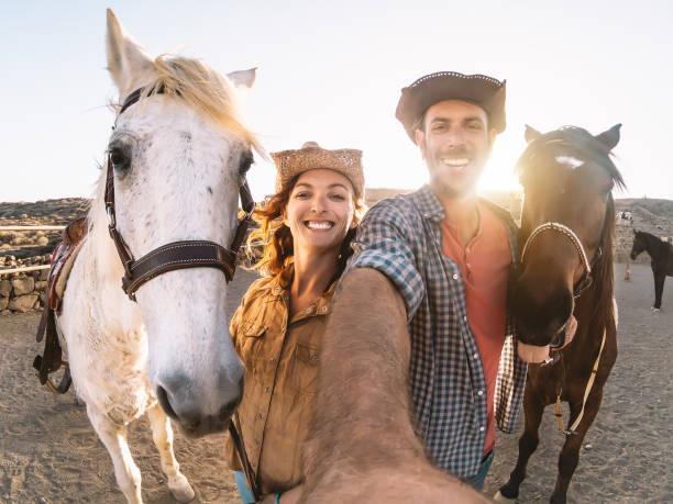 glückliches paar macht selfie mit pferden im stall - junge bauern mit tieren in corral ranch spaß haben - mensch und tiere beziehung lifestyle-konzept - landwirtschaftlicher beruf stock-fotos und bilder