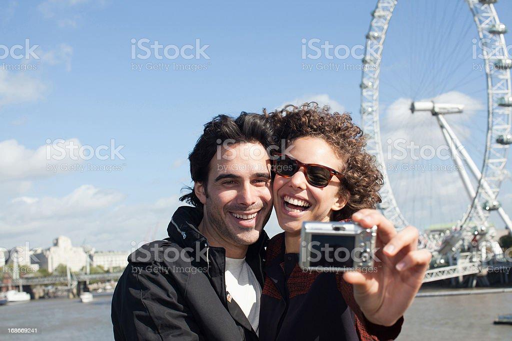 Happy couple taking self-portrait with digital camera near ferris wheel royalty-free stock photo
