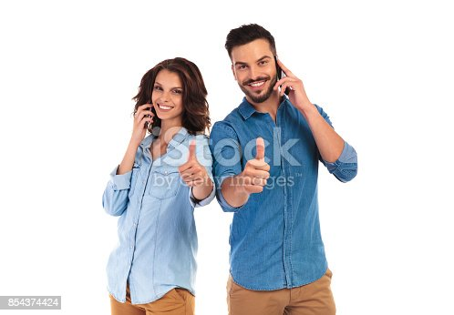 854381780istockphoto happy couple talking on phones and make the ok sign 854374424