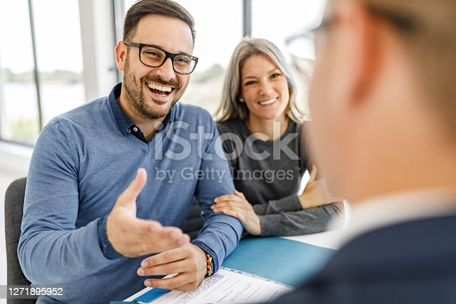 Young happy couple communicating with their insurance agent during a meeting in the office.