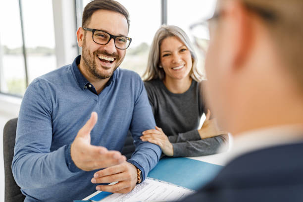 Happy couple talking to their bank manager on a meeting in the office. stock photo