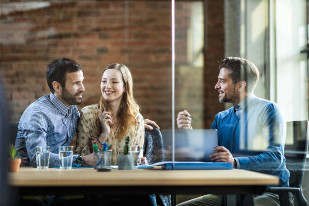 Happy couple talking to their insurance agent in the office. stock photo
