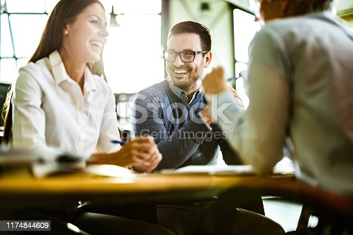 Young happy couple communicating with their financial advisor on a meeting in the office. Focus is on man.