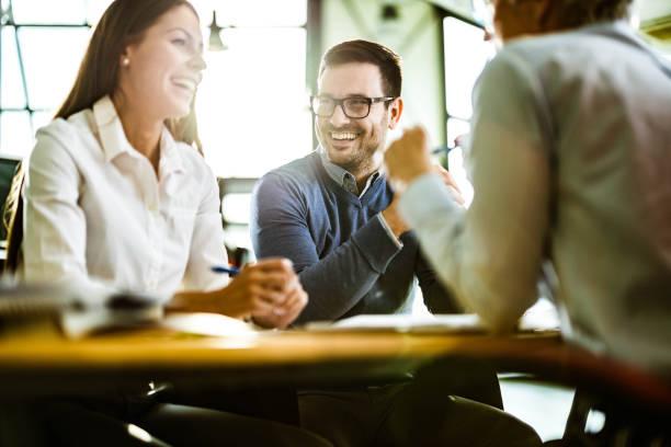 lyckligt par pratar med sin försäkringsagent på ett möte på kontoret. - client meeting bildbanksfoton och bilder