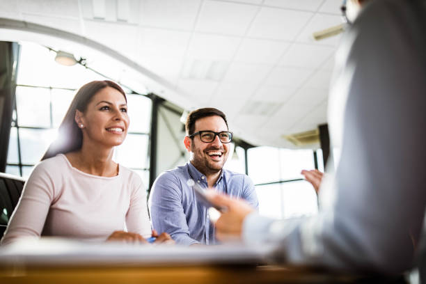 Happy couple talking to their insurance agent on a meeting in the office. stock photo