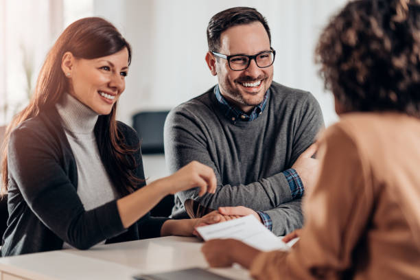 Happy couple talking with sales manager stock photo