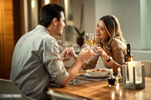 istock Happy couple toasting with Champagne during dinner at dining table. 1208378663