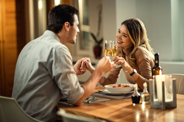 Happy couple toasting with Champagne during dinner at dining table. Happy woman and her boyfriend holding hands while toasting with Champagne while having dinner at dining table. romantic activity stock pictures, royalty-free photos & images