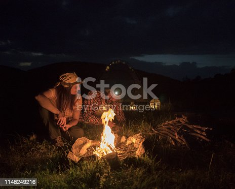 Happy young couple tourists having fun in the Nature at Night. Sitting next to the Campfire, Cooking on Headlight. Joy. Illuminated by the Fire