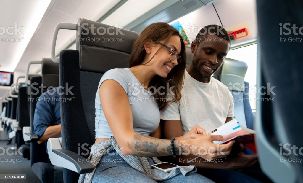 Portrait of a happy couple traveling by train and reading a travel...