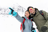 Portrait of a happy couple trekking in the snow and pointing away while smiling - winter lifestyle concepts