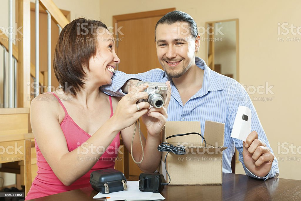 Happy couple unpacking new digital camera royalty-free stock photo