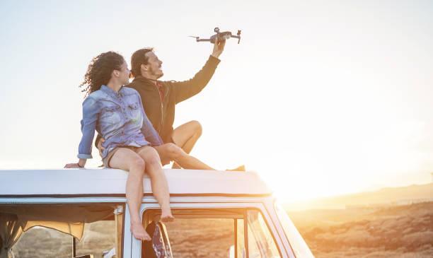 brautpaar mit einer drohne sitting on top of vintage minivan bei sonnenuntergang - junge leute, die spaß mit neuen technologischen trends während der ferien - reisen, tech und urlaub konzept - fokus auf körper - flugdrohne stock-fotos und bilder
