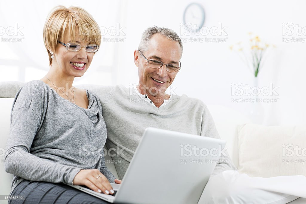 Happy couple using a laptop together at home royalty-free stock photo